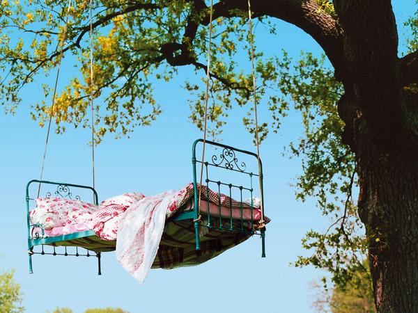 Ein Bett hängt in einem Baum